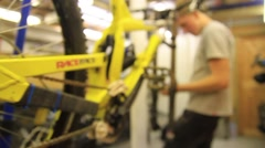 Panning dolly tracking shot of a man working on his mountain bike in a workshop. Stock Footage