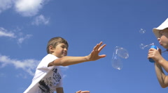 Girl blowing bubbles, a boy trying to catch soap bubbles, slow motion Stock Footage