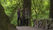 Friends Talk Beneath Large Tree On A Nature Trail Stock Footage