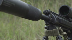 Black sniper rifle is on the ground in the grass. airsoft guns Stock Footage