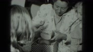 1949: smiling mother opening birthday present at party attended by family  Stock Footage