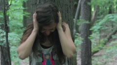 A girl covering her ears and hiding behind trees in a forest. Stock Footage