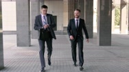 Two young businessmen walking to the office together Stock Footage