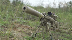 Camouflage sniper rifle is on the ground in the grass. airsoft guns Stock Footage