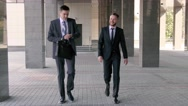 Two handsome businessmen chatting together as they walk along the office Stock Footage