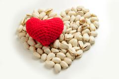 Pistachios and Knitting yarn to form a red heart. Stock Photos