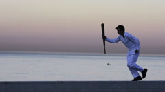 LS MS PAN of a man running with a simulated Olympics torch. Stock Footage