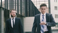 Close-up of young businessmen walking against the business center background Stock Footage