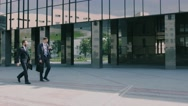 Two confident coworkers walking to work on a sunny morning Stock Footage