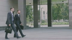 Two confident young businessmen are walking in the urban environment the office Stock Footage