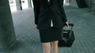 Close-up of an attractive blond businesswoman walking with travel luggage Stock Footage