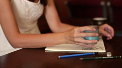 Young woman draws and drinks water in a cafe-4 Stock Footage