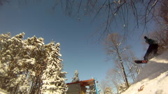 A young man snowboarding through trees and jumping over a playhouse. Stock Footage