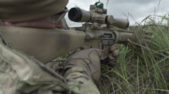 Sniper lies behind cover in the grass with a gun in his hand and shoots Stock Footage