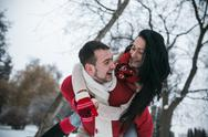 Man and woman having fun in the snow-covered park Stock Photos
