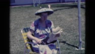 1951: women reading newspaper by clothesline in funny broad brimmed hat FLORIDA Stock Footage