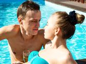 Couple has a rest in the pool with champagne. they are smiling, hugging and Stock Photos