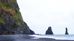 View of Reynisdrangar rock formation from Reynisfjara beach at ViK in Iceland Stock Footage
