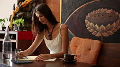 Young woman draws and drinks water in a cafe-3 Stock Footage
