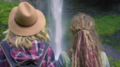 Hikers Watch Waterfall, Woman Turns And Smiles At Her Friend Stock Footage