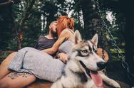 Beautiful couple together with dog on a swing Stock Photos