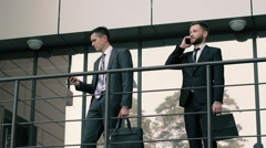 Two elegant businessmen doing business on the mobile phones standing near Stock Footage