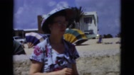 1951: lady in dress, glasses and hat and man in bathing suit at the beach  Stock Footage