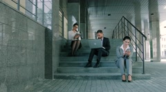 Young business people working on stairs using laptop, tablet and smartphone Stock Footage