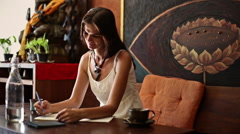 Young woman draws and drinks water in a cafe-2 Stock Footage