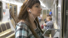 Woman in underground listening to music with phone Stock Footage