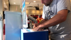 Man scratching lottery ticket nside Petro-Canada gas station convenient store Stock Footage