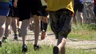Competition participants athlete people running through grass Stock Footage