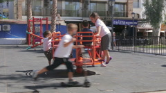 Children ride on the carousel in the summer park Stock Footage