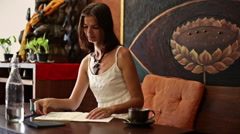 Young woman draws and drinks water in a cafe-5 Stock Footage