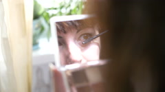 Young Woman Looking in the Mirror and Colors the Eyes, Wear Make Up Stock Footage