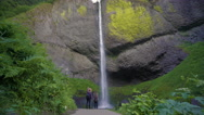 Hikers Stand Beneath Waterfall At Edge Of Trail, They Gesture And Talk About It Stock Footage
