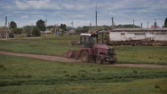 Tractor ploughing a field next to a village farm Stock Footage