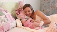 Young mother playing with her little baby on the bed - indoors Stock Footage