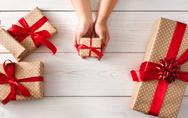 Woman's hands give christmas gift in present box Stock Photos