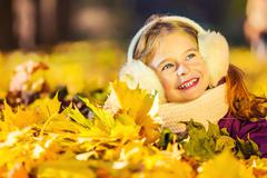 Little girl in earflaps playing with autumn leaves Stock Photos