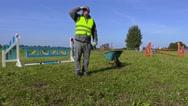 Tired horse handler with wheelbarrow on hurdle field Stock Footage