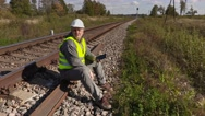 Railroad worker on the rails using tablet Stock Footage
