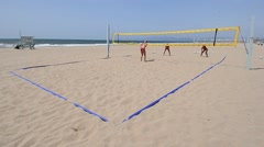 Establishing master shot of women beach volleyball players jump serving. Stock Footage