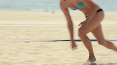 Close-up tracking panning shot of a female beach volleyball player diving for th Stock Footage