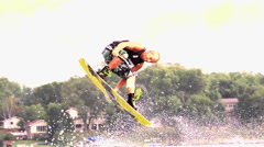 A man doing a jump and board grab while wakeboarding on a lake. Stock Footage