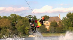 A man doing a jump and flip while wakeboarding on a lake. Stock Footage