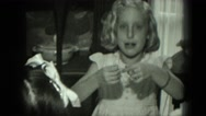 1951: birthday girl opens presents and examines them with onlookers present Stock Footage