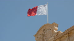 Flag of Malta in front of blue sky floating on flag pole. 4K footage Stock Footage