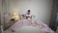 Beautiful woman in a shirt talking on the phone morning the luxurious bedroom Stock Footage