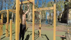Young man exercising in outdoor gym Stock Footage
